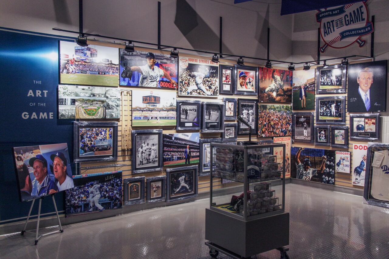 A display case in front of a wall of Dodger Stadium sports art.
